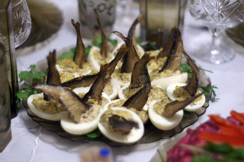 The original salad of stuffed pate eggs with sprats. The original design of smoked fish salad. The basis is the halves of chicken eggs, filled with chicken royalty free stock images
