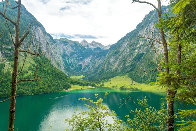 Konigssee上部湖看法有清楚的绿色水、反射、山、天空背景和码头的Salet Alm,巴伐利亚,德国 免版税图库摄影