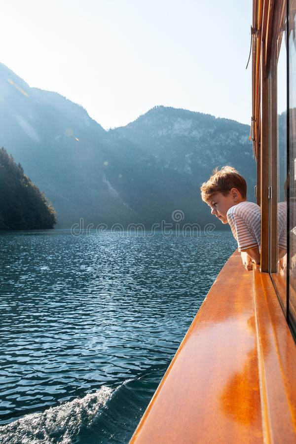 Konigssee lake, Bavaria - August 19, 2018: Unknown boy looking at green water of Konigssee, known as Germany deepest and royalty free stock photography