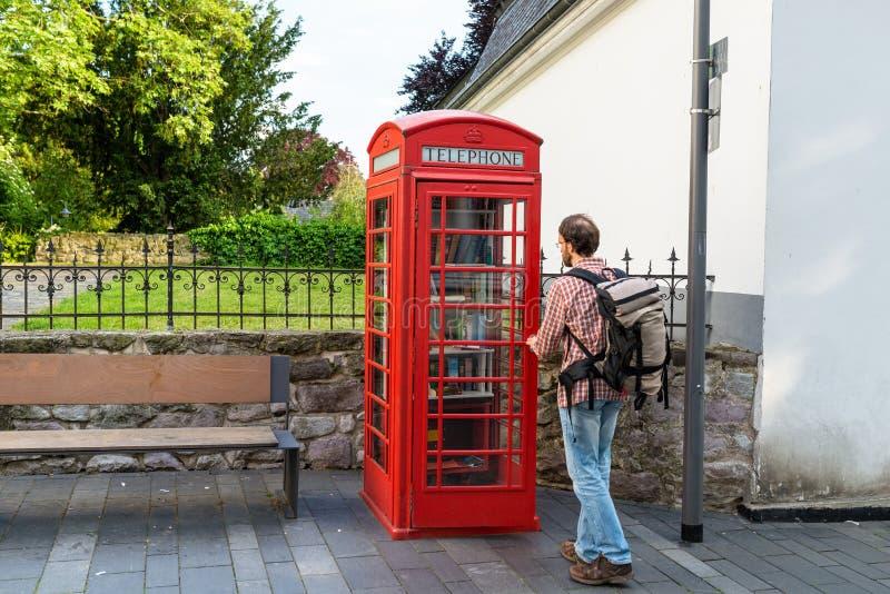 Konigswinter, Duitsland - 23 Mei 2019 Een rode telefooncel voor de vrije uitwisseling van boeken Een mens die een boek in een tel stock fotografie