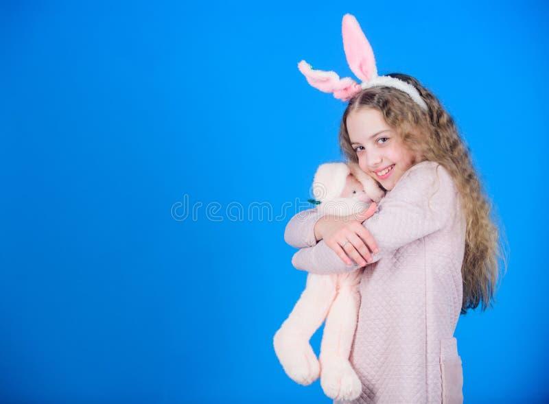 Konijntjesmeisje met leuk stuk speelgoed op blauwe achtergrond Kind het glimlachen het stuk speelgoed van het spelkonijntje Geluk stock foto
