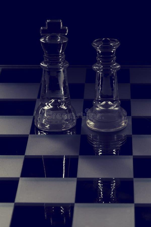 Koning en koninginglasschaakstuk die elkaar in zwart-wit onder ogen zien stock foto