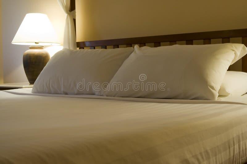 Koning gerangschikt bed in een hotelruimte stock afbeelding