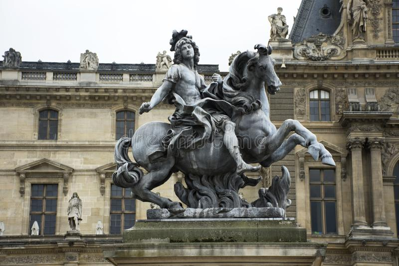 Koning Louis XIV Standbeeld in Cour Napoleon de ingang aan Musee du Louvre royalty-vrije stock foto's