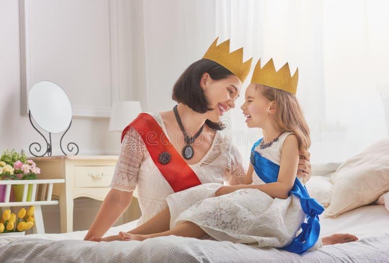 Koningin en prinses in gouden kronen stock foto's