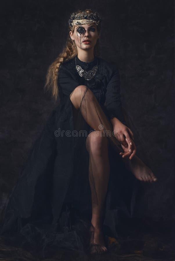 Koningin van duisternis in zwart fantasiekostuum op donkere gotische achtergrond Het hoge model van de manierschoonheid met donke royalty-vrije stock fotografie