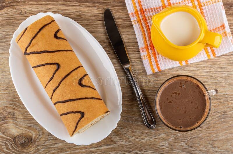 Koninginnenbrood in schotel, mes, kruik melk op servet, cacao met melk in kop op lijst Hoogste mening royalty-vrije stock afbeelding