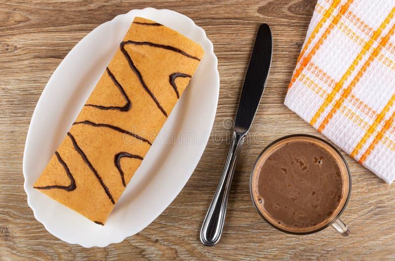 Koninginnenbrood in schotel, mes, servet, cacao met melk in kop op houten lijst Hoogste mening stock foto