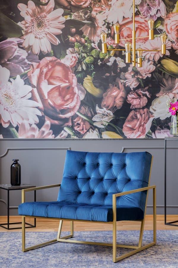 Koningsblauwenleunstoel met gouden kader die zich op tapijt in echt p bevinden stock foto
