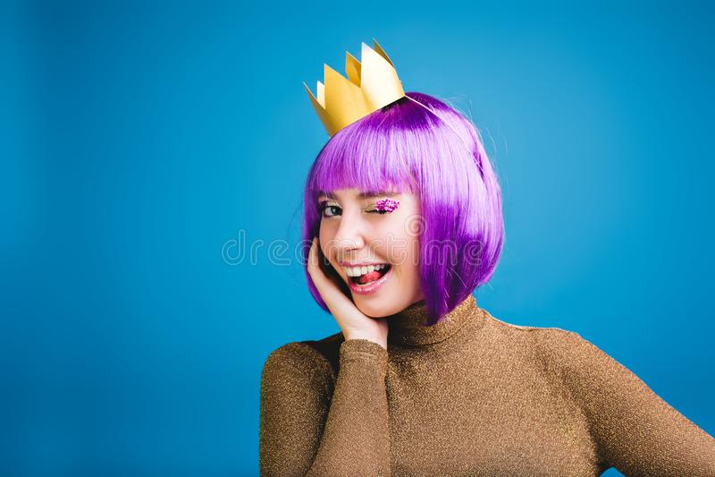 Koninklijk portret van blije jonge vrouw in luxekleding, gouden kroon die pret op blauwe achtergrond hebben Het tonen van tong stock foto