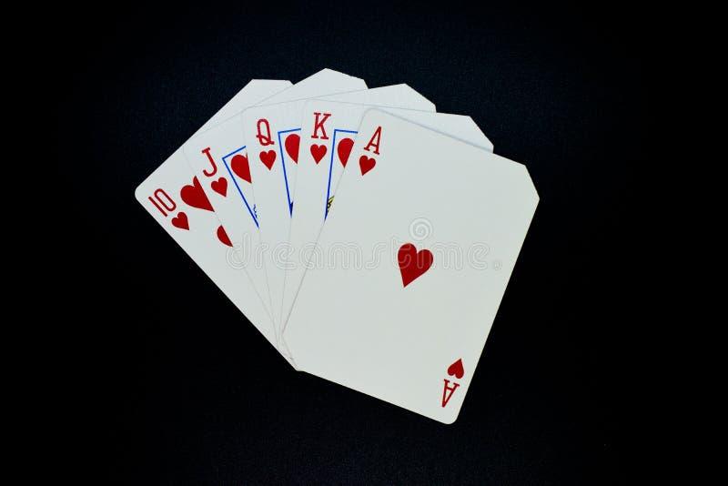 Koninklijke gelijke rechte vloed van hartenkaarten in pookspel tegen zwarte achtergrond stock afbeeldingen
