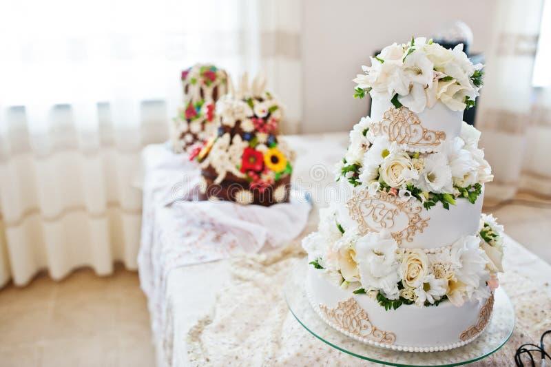 Koninklijke huwelijkscake met bloemen op lijst stock afbeelding
