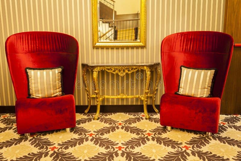 Koninklijke Leunstoel in rood in warme athmospheredecoratie stock fotografie