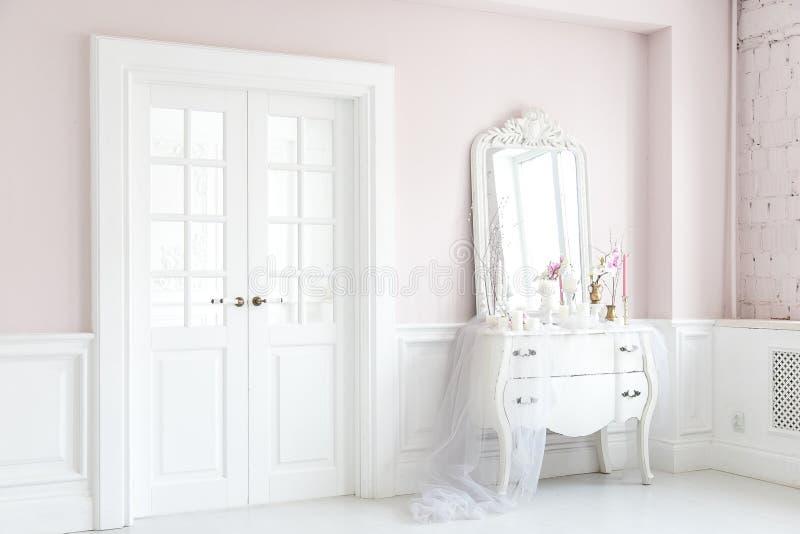 Koninklijke slaapkamer Plaats voor samenstellingsmeisjes Elegante witte toilettafel met spiegel in licht klassiek luxebinnenland stock afbeelding