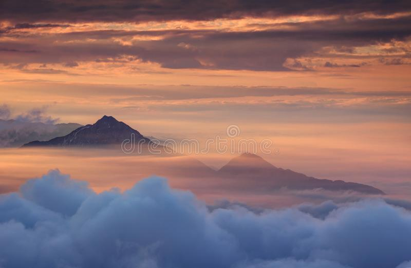 Konische Berge im Herbstnebel und im roten Himmel morgens stockfotos