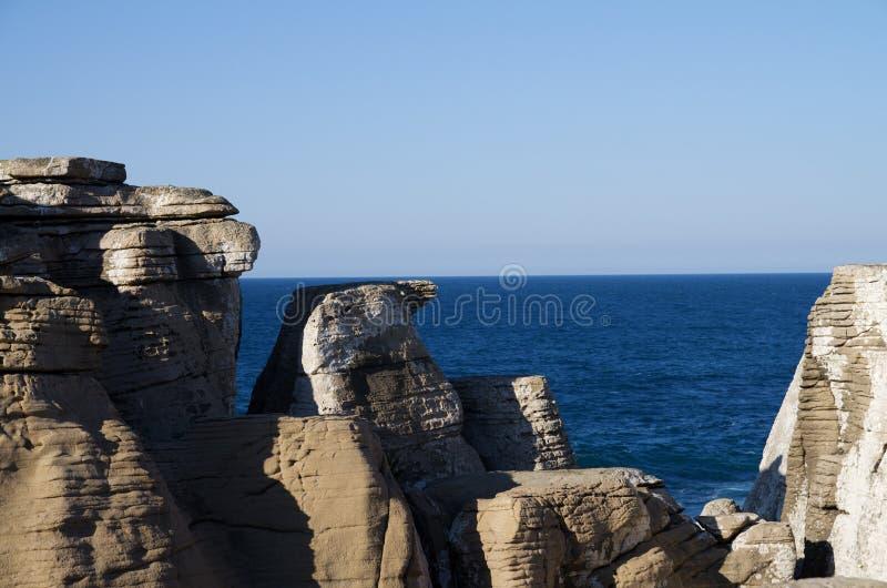 Konische Felsen gegen den Ozean stockfotografie
