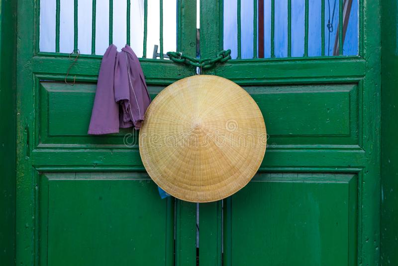 Konisk hatt för asiatisk stil som hänger på en grön dörr i Vietnam fotografering för bildbyråer