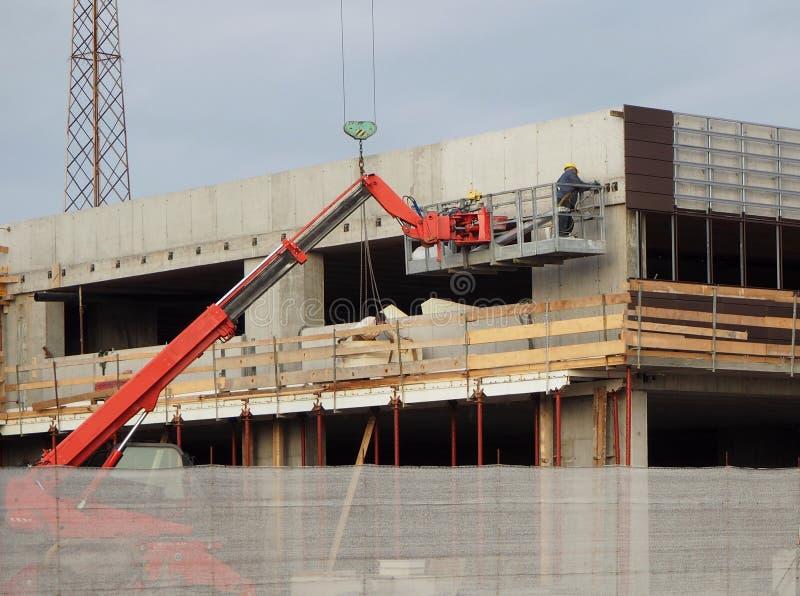 Konjunktur im Bausektor Kirschpflücker bei der Arbeit über eine Fassade eines Neubaugebäudes lizenzfreie stockfotos