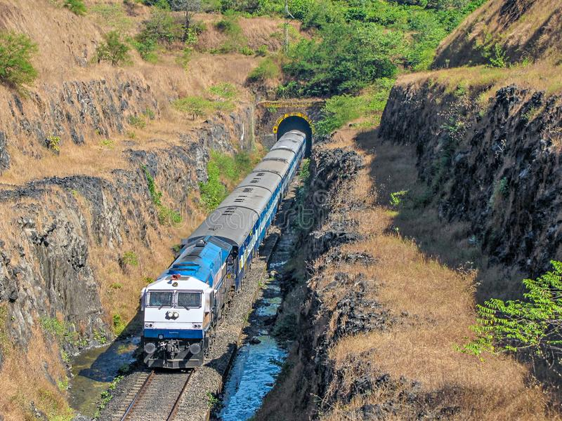 Train coming out of a tunnel in Konkan region of Maharashtra, India. stock images