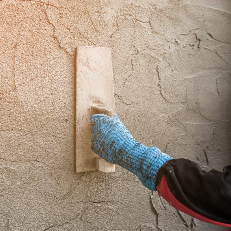 Konkret arbetare för stuckatör på väggen av huset arkivbild