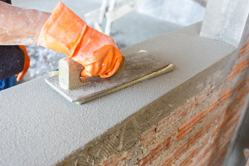 Konkret arbetare för stuckatör på väggen av huskonstruktion arkivfoton