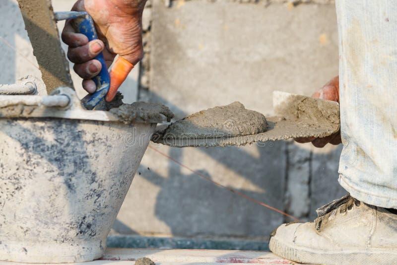 Konkret arbetare för stuckatör på väggen av huskonstruktion royaltyfria bilder