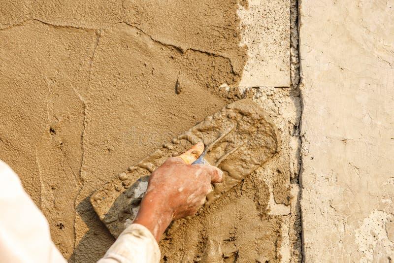 Konkret arbetare för stuckatör på väggen av huskonstruktion royaltyfri fotografi