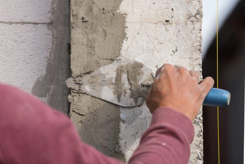 Konkret arbetare för stuckatör på väggen av huskonstruktion arkivbild