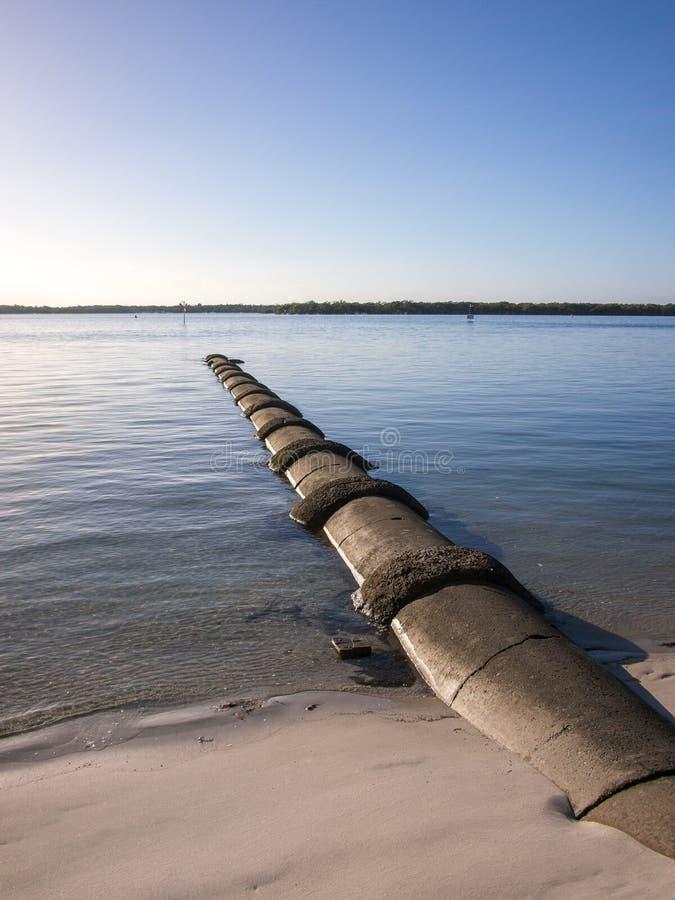Konkret avrinning för avklopprör som in går till floden arkivbilder