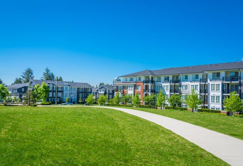 Konkret bana över enorm grön gräsmatta framme av bostads- andelsfastighetbyggnad arkivfoto