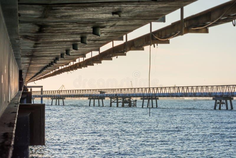 Konkret bro över havsvatten med soluppgång arkivbilder