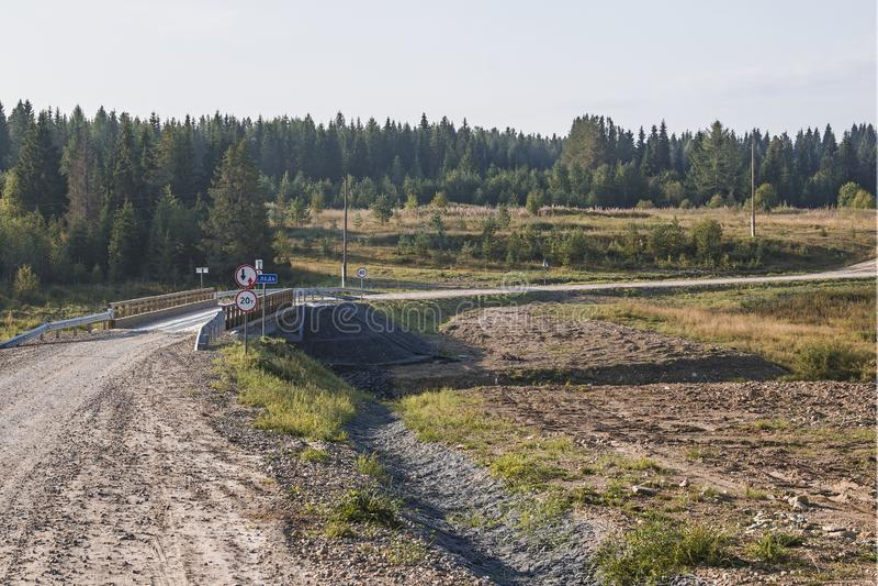 Konkret bro med träräkningen som läggas över floden som ledas, i deras oändliga Arkhangelsk region, rysk federation, 2018 royaltyfri bild