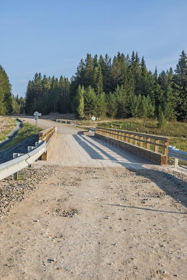 Konkret bro med träräkningen som läggas över floden som ledas, i deras oändliga Arkhangelsk region, rysk federation, 2018 arkivfoto