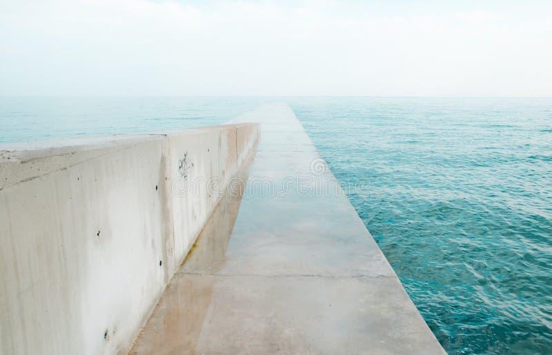 Konkret skeppsdocka som ut sträcker till havet arkivfoton
