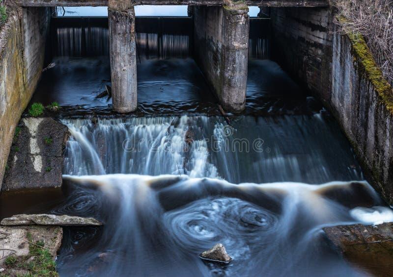 Konkret struktur av den gamla flodfördämningen Vatten som är suddigt vid långt e fotografering för bildbyråer