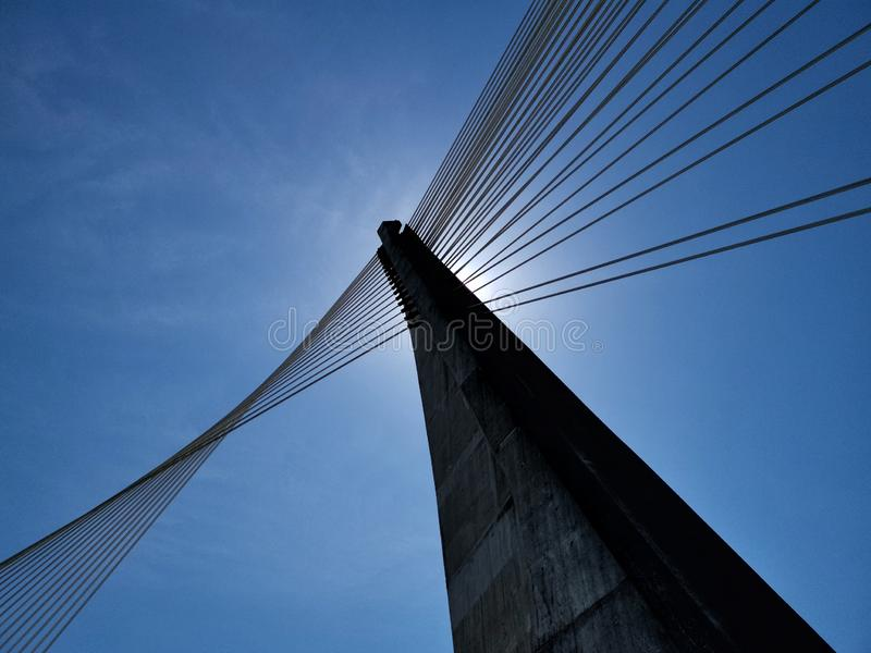 Konkret struktur med stålhänglsen av en bro över en flod under en intensiv blå himmel royaltyfria foton