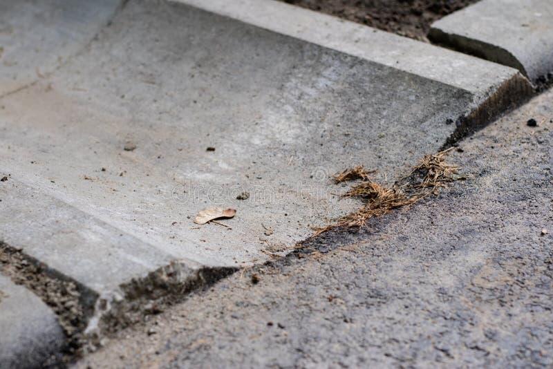 Konkret utflöde av vatten på en asfaltväg Ett välformat ställe fo royaltyfria foton