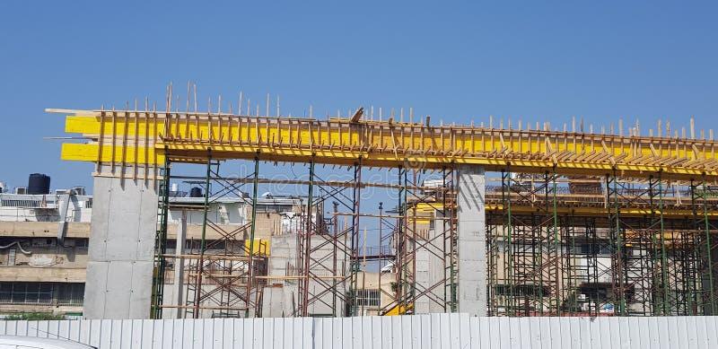 Konkreta kolonner belägger med metall strålar och trämaterialet till byggnadsställning för framtida byggnad royaltyfri foto