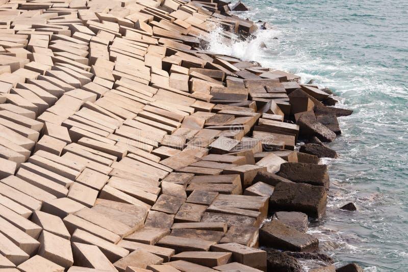 Konkreta kvarter som bildar skyddande kust- skyddsmur mot havet royaltyfri bild