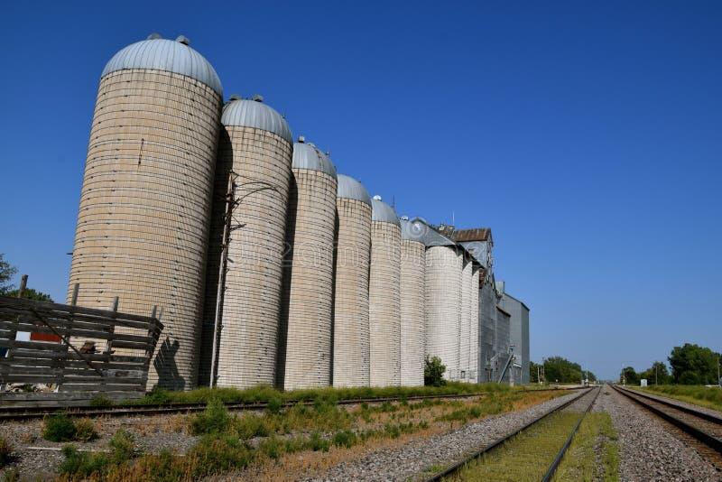 Konkreta silor som används som kornlagring av ett järnvägspår arkivbild