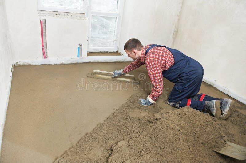 Konkrete Arbeitskraft des Gipsers bei der Bodenarbeit lizenzfreies stockbild
