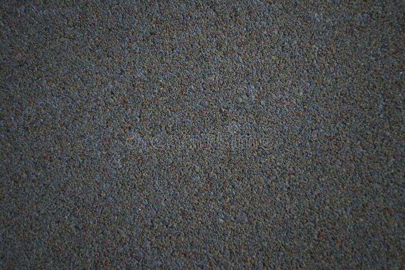 Konkrete Beschaffenheit mit unscharfen Rändern Horizontaler Hintergrund des dunkelgrauen konkreten Bodens mit vielen kleinen Stei lizenzfreies stockbild
