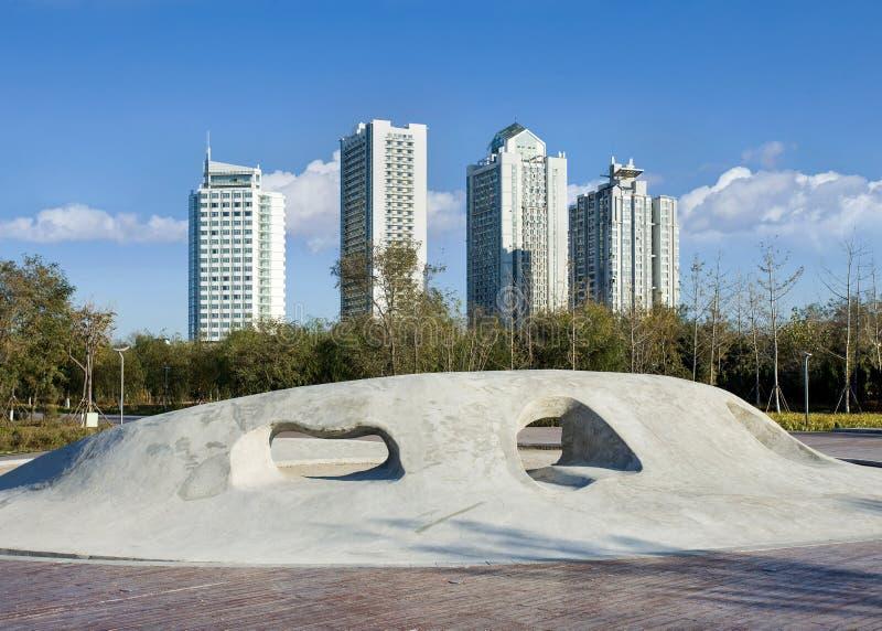 Konkrete Skulptur in einem Park mit Ebenen auf dem Hintergrund, Yantai, China lizenzfreies stockfoto