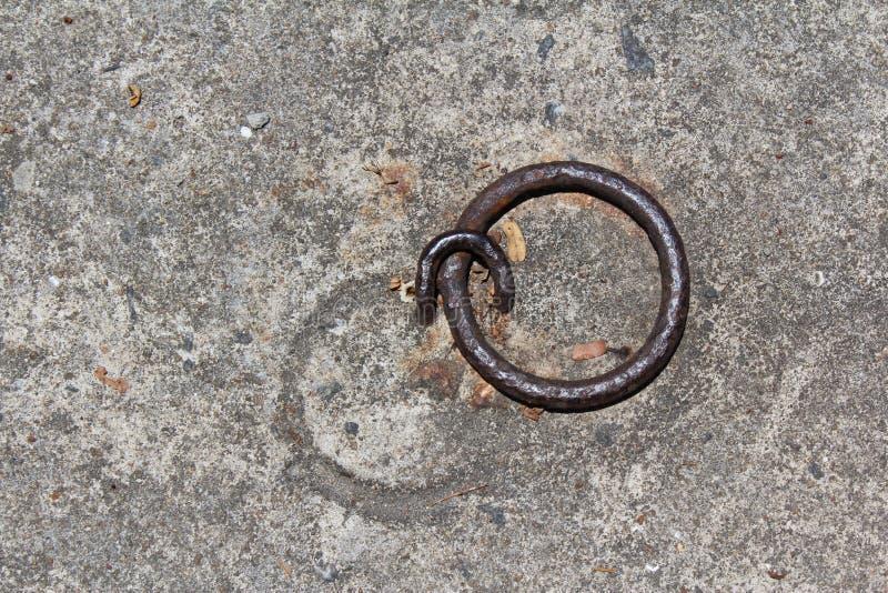 Konkreter Boden mit rostigem Ring und Schleife des Eisens stockfoto