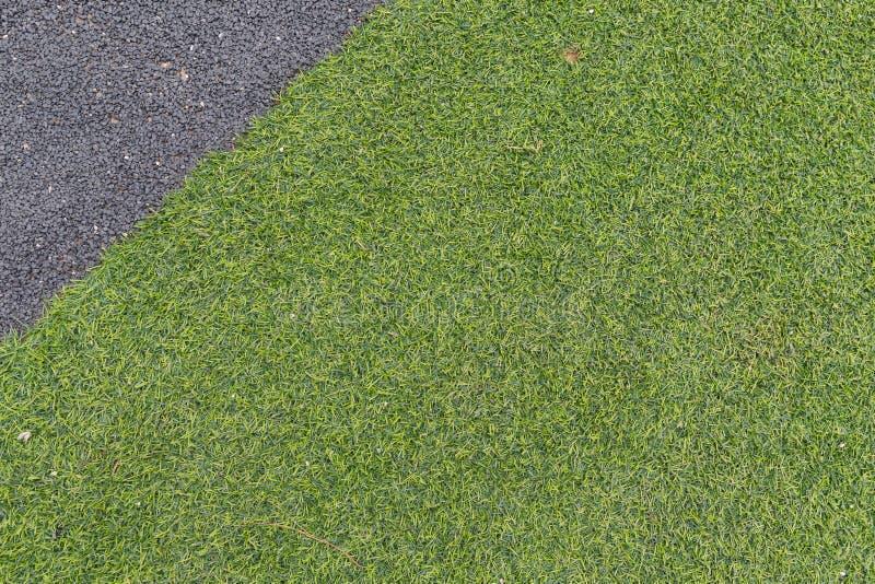 Konkreter Hintergrund des grünen Grases und des Kieses, dekoratives Äußeres lizenzfreie stockfotos