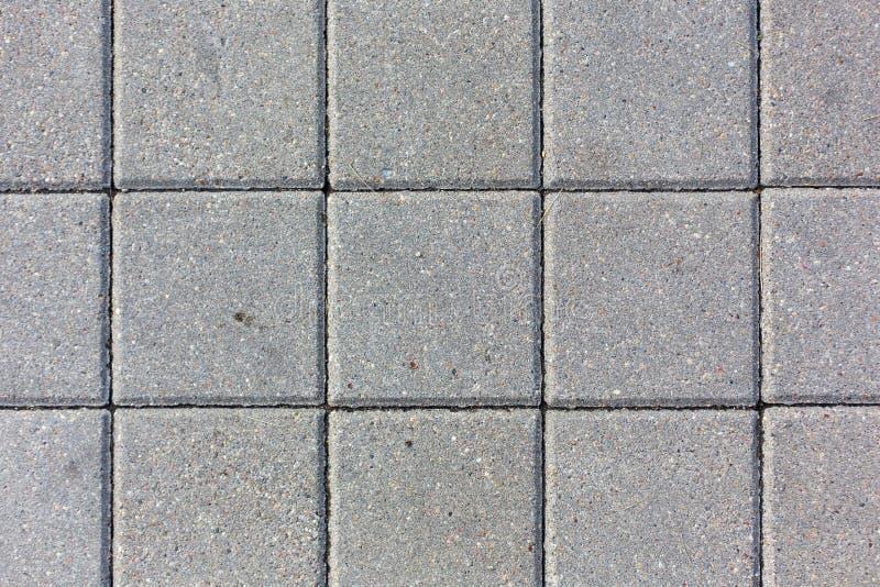 Konkretes Quadrat deckt Musterbeschaffenheitshintergrund mit Ziegeln stockbild