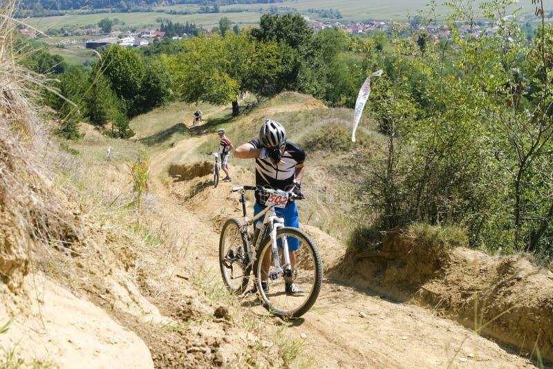 Konkurent pcha jego rower na wzg?rzu obraz royalty free