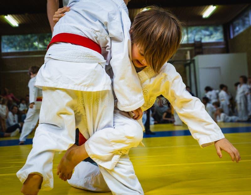 Konkurrens på judoskola, två lilla brottas pojkar i kampen, närbild royaltyfri fotografi