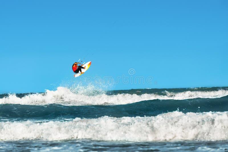 konkurrensar som dyker pölsportar som simmar vatten Kiteboarding Kitesurfing Surfare som surfar vågor A royaltyfri foto