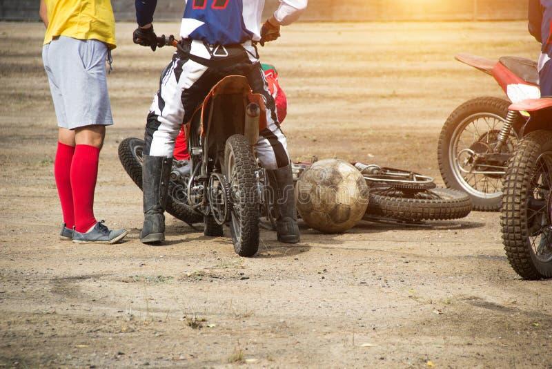 Konkurrenser på motoball, spelare slåss ursinnigt för bollen som spelar fotboll på motorcyklar, motorcykeln royaltyfri foto